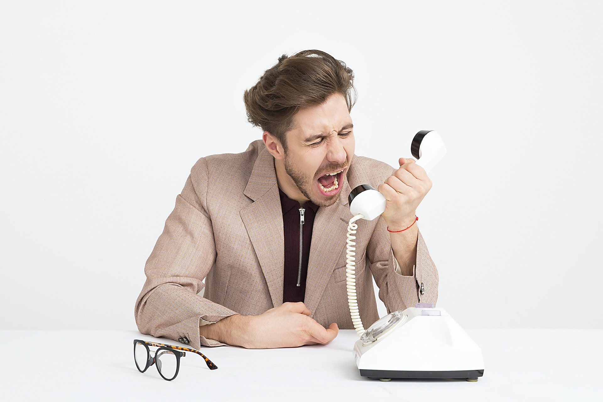 man in tan suit holding a landline phone yelling into it